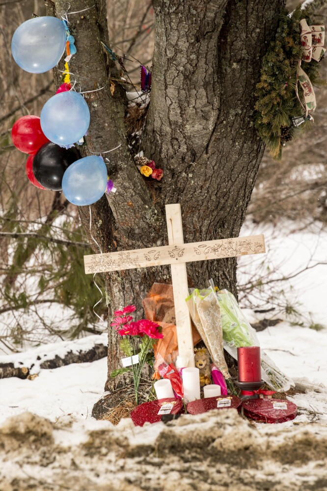 Mourners have left a cross and other items around a large pine tree on Hinckley Road in Clinton, where three youths were killed Sunday morning in a one-car accident.
