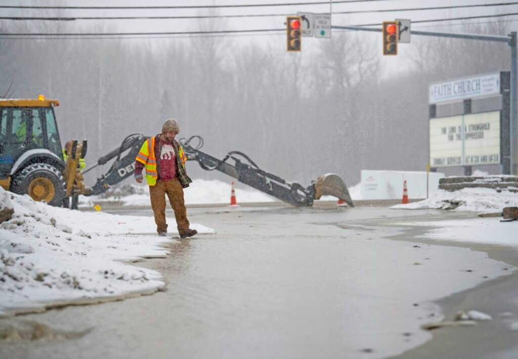 Justin Hort, a utility locator for USIC, stands next to a small river as crews work to repair a water main break Tuesday at the entrance of Shaw's Plaza on Kennedy Memorial Drive in Waterville.