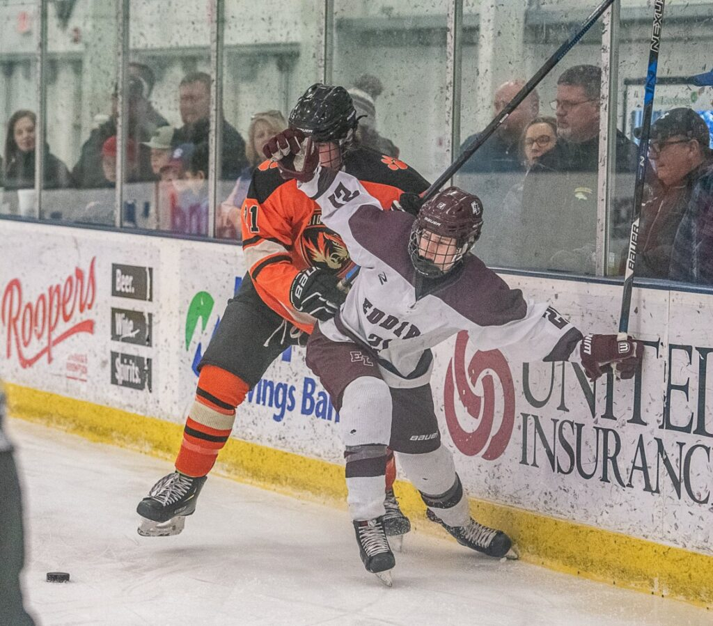 Edward Little's Campbell Cassidy and Biddeford/Massabesic/Old Orchard Beach's Brayden Locke scuffle near the board during Tuesday's Class A boys hockey preliminary playoff game in Auburn.