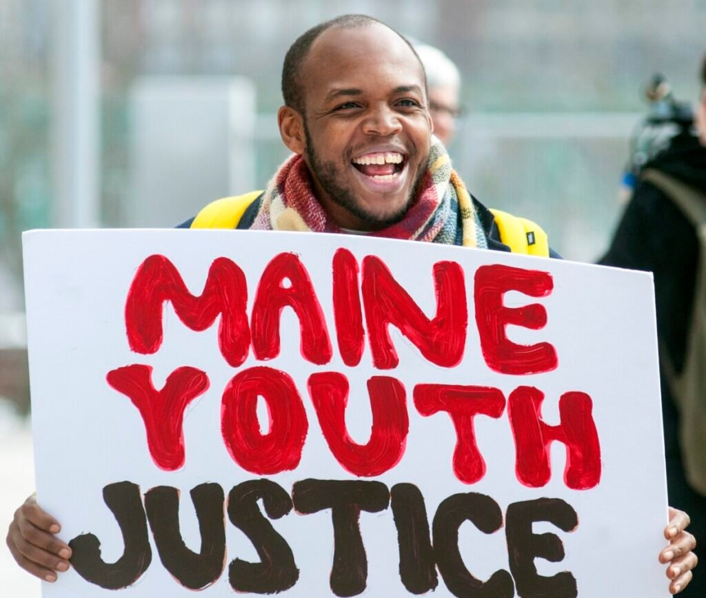 Darryl Shepherd Jr. of Biddeford carries a sign as he leads call-and-response cheers during Maine Youth Justice's event Tuesday in Augusta. Youth activists are demanding that the state immediately shut down the Long Creek Youth Development Center.