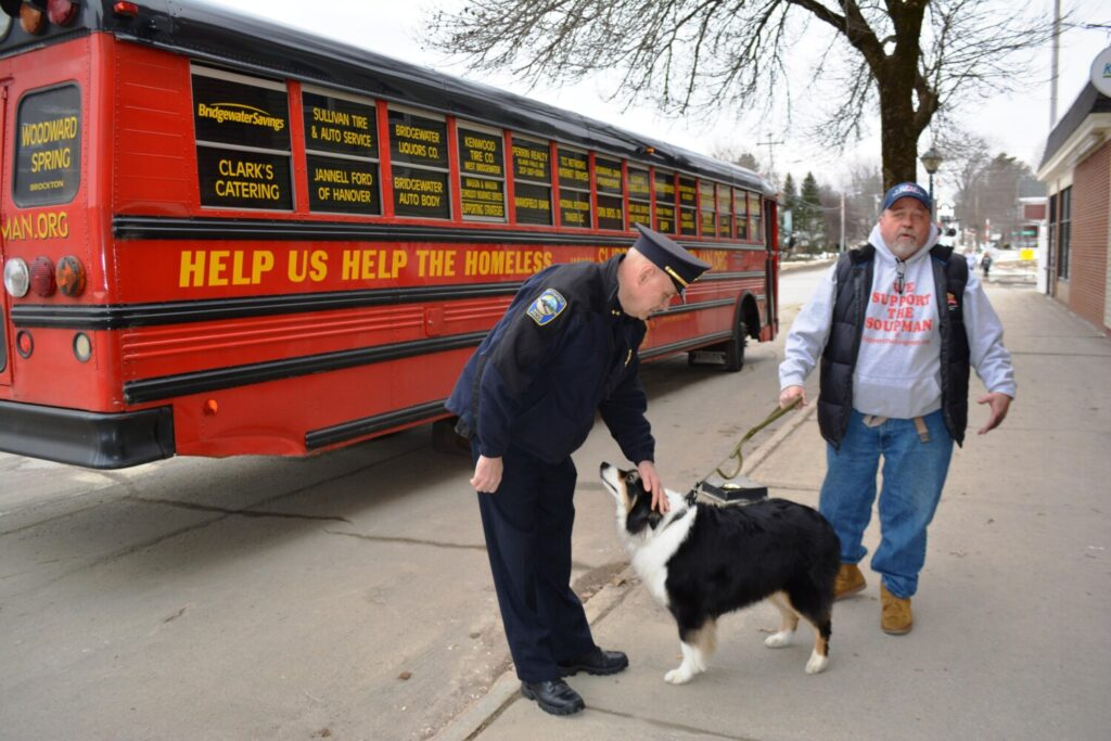 Pittsfield Police Chief Pete Bickmore, left, greets Koji, the Soupman's support dog, and Peter Kelleher, the Soupman. Kelleher stopped in Pittsfield on Feb. 5 to drop off 170 homeless survival packs for the needy in the area.