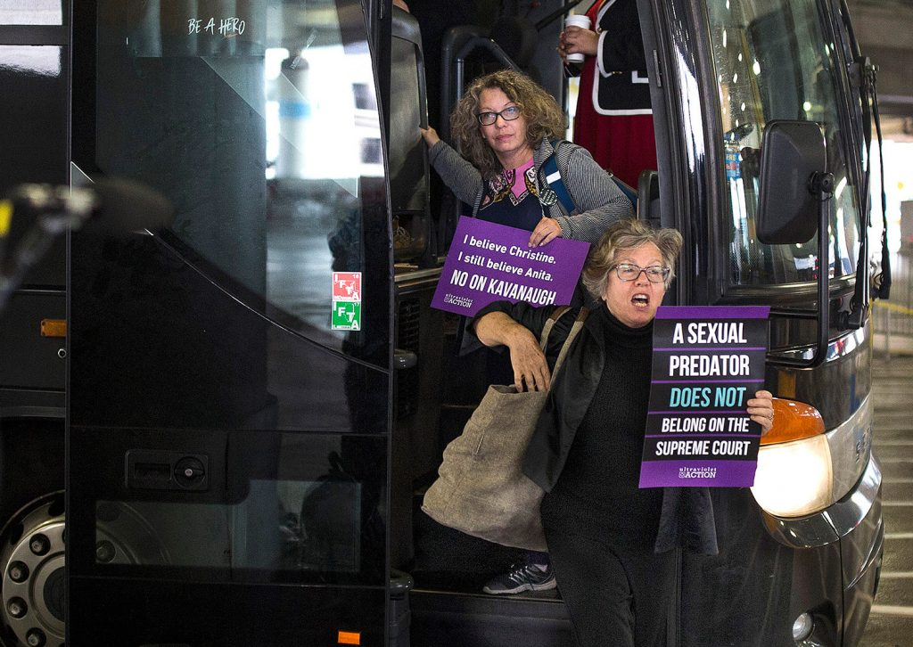 "Susan Feiner, front, gets off a bus at Union Station in Washington, D.C., with a group of Mainers on Oct. 4, 2018. The group traveled from Maine in hopes of meeting with Sen. Susan Collins to voice opposition to then-Supreme Court nominee Brett Kavanaugh. Feiner, a retired USM professor, was later barred from teaching because she offered students a ""pop-up"" course for credit to take the bus to D.C. with demonstrators."