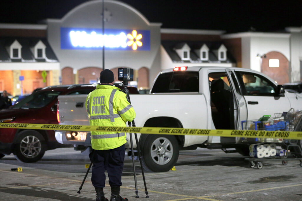 An investigator sets up survey equipment at the scene of Friday's shooting in the parking lot of the Walmart in Scarborough.