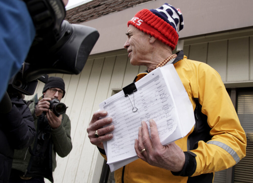 Precinct captain Carl Voss of Des Moines holds voter registration forms that he tried to deliver to the Iowa Democratic Party headquarters in Des Moines on Tuesday. He found the headquarters unstaffed.