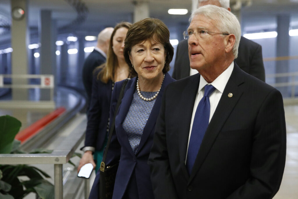 Sen. Susan Collins, R-Maine, walks with Sen. Roger Wicker, R-Miss., on Wednesday during the impeachment trial of President Trump on charges of abuse of power and obstruction of Congress. The Senate acquitted Trump of both charges.
