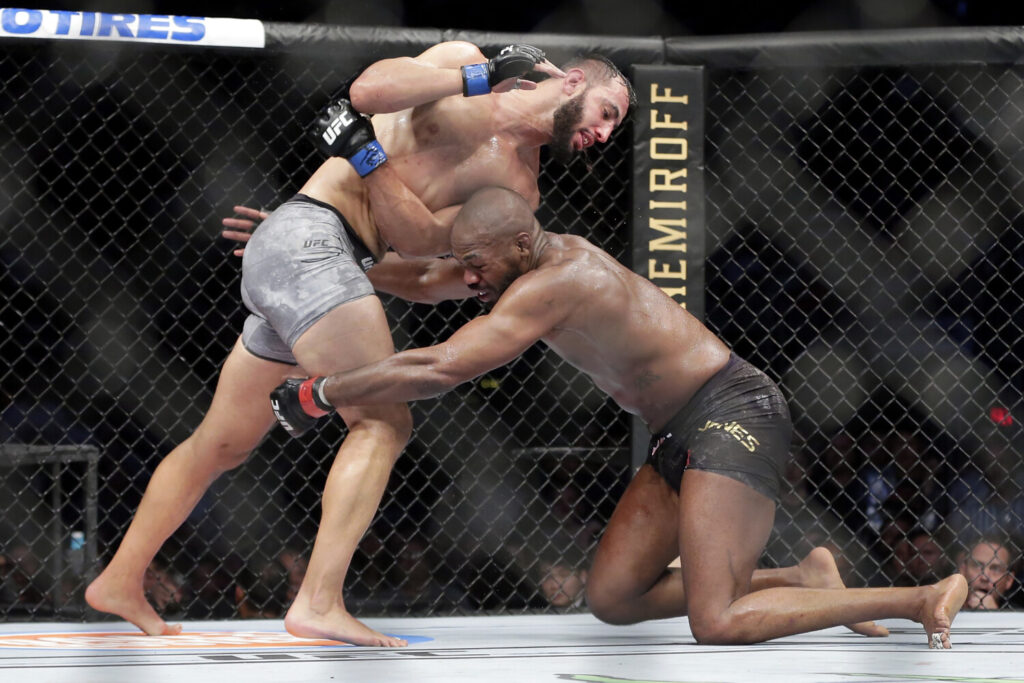 Jon Jones, right, goes for a take down of Dominick Reyes during their UFC light heavyweight fight on Saturday in Houston. Jones won in a unanimous decision in a fight many feel he lost.