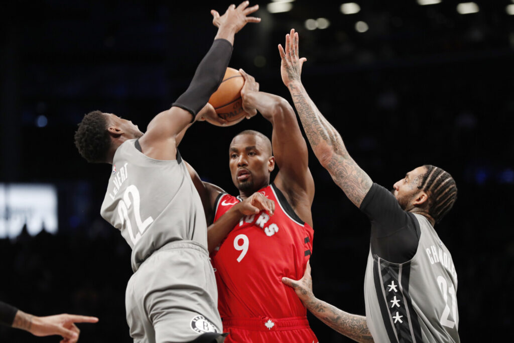 Brooklyn's Caris LeVert, left, and Wilson Chandler defend Toronto's Serge Ibaka during Wednesday's game in New York.