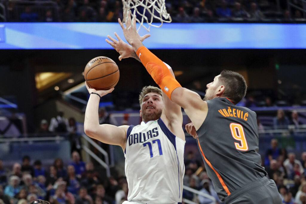 Luka Doncic, left, of Dallas, shoots over Orlando's Nikola Vucevic during Friday's game in Orlando, Fla.