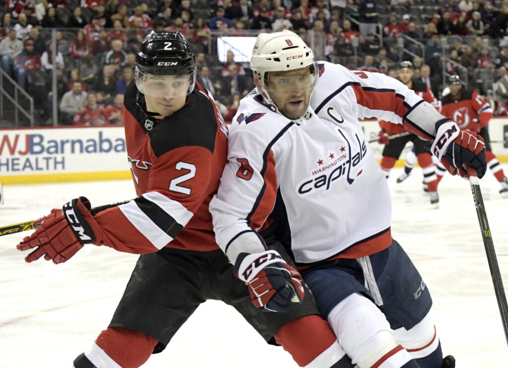 Washington left wing Alex Ovechkin, right, battles New Jersey defenseman Colton White during Saturday's game  in Newark, N.J. Ovechkin's goal in the third period to made the score 2-2 and was the 700th of his career.