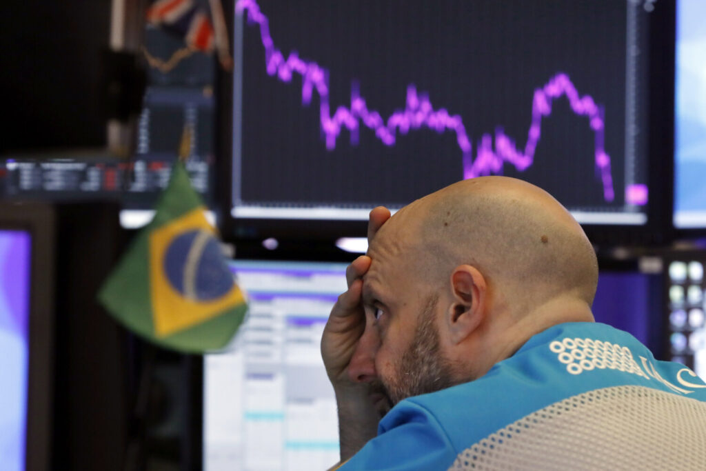 Specialist Meric Greenbaum works at his post on the floor of the New York Stock Exchange on Tuesday, Stocks slumped and bond prices soared for the second day in a row as fears spread that the widening virus outbreak will put the brakes on the global economy.