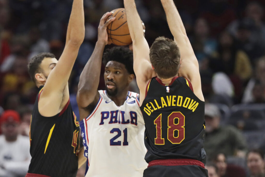 Philadelphia's Joel Embiid, center, squeezes between Cleveland's Ante Zizic, left, and Matthew Dellavedova during Wednesday's game in Cleveland.