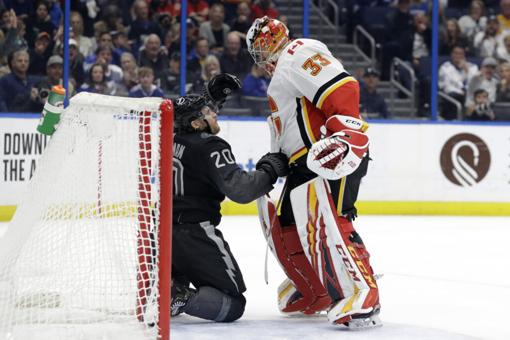 Calgary Flames goaltender David Rittich knocks down Tampa Bay Lightning center Blake Coleman after the two collided Saturday in Tampa, Fla.