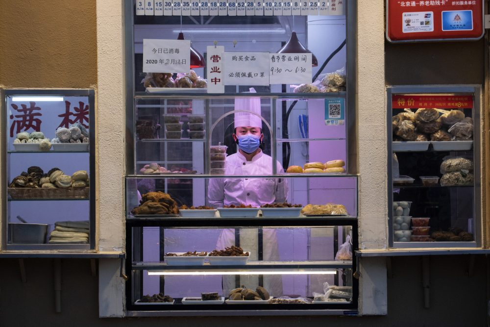A chef looks out from behind a display of food products at a restaurant in Beijing, China. Regulators on Monday promised tax cuts and other aid to help companies recover from China's virus outbreak.