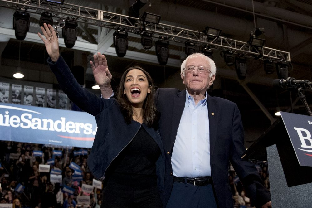 Democratic presidential candidate Bernie Sanders, accompanied by Rep. Alexandria Ocasio-Cortez, D-N.Y., takes the stage at a campaign stop at the University of New Hampshire on Monday, a day before the state's primary election.