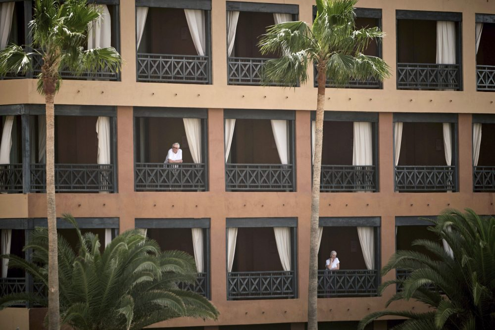 People stand at their balconies at the H10 Costa Adeje Palace hotel in Tenerife, Canary Island, Spain, on Tuesday. Spanish officials say a tourist hotel on the Canary Islands has been placed in quarantine after an Italian doctor staying there tested positive for the new coronavirus.