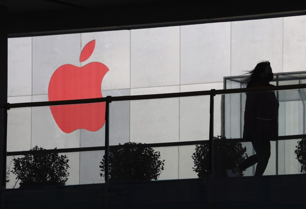 A woman runs past a Apple logo colored red in Beijing, China. Apple is temporarily closing its 42 stores in mainland China, one of its largest markets, as a new virus spreads rapidly and the death toll there rose to 259.