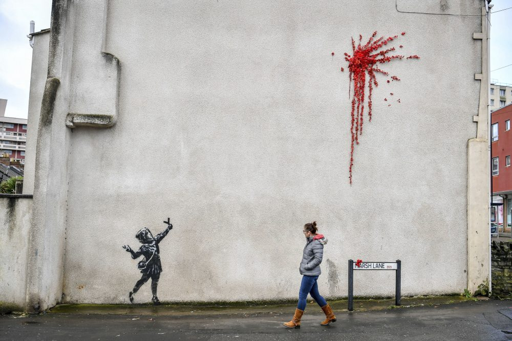 A woman walks past Banksy's newest mural  on the side of a house in Bristol, England, on Thursday. The art has since been covered after it was defaced.