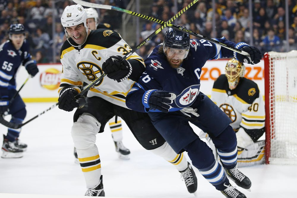 Winnipeg Jets' Blake Wheeler (26) and Boston Bruins' Zdeno Chara (33) chase the puck as goaltender Tuukka Rask (40) watches during the second period of a January 2020 game in Winnipeg, Manitoba.