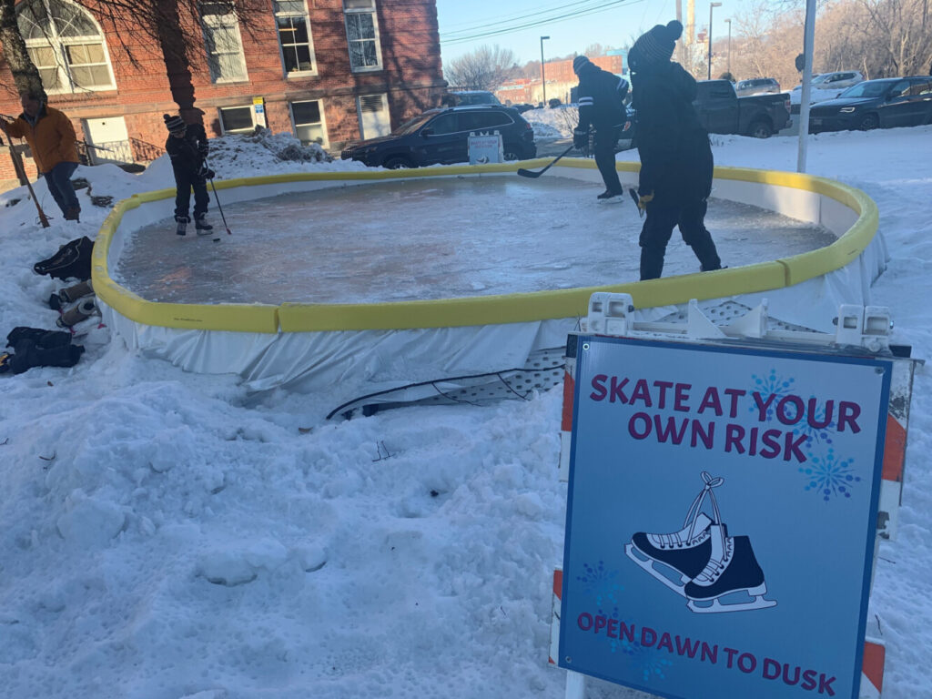 """Cutting some time on the ice on a frigid Friday afternoon are, from left, Eddie Goff, 11, of Norridgewock, John Robertson, 46, of Waterville, and Noah Robinson, 11, of Waterville. Bert Languet, """"The Iceman"""" off the rink to the left, donated the rink to the Children's Discovery Museum and helped set it up."""