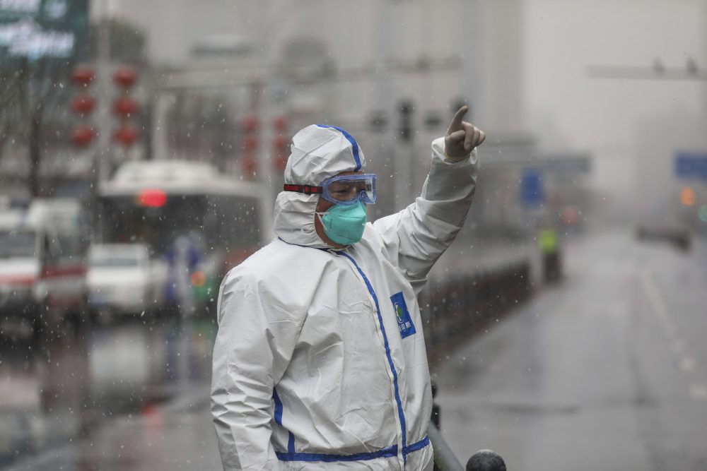 A worker wearing a protective suit gestures to a driver outside a hospital newly designated to treat COVID-19 patients in Wuhan, China, on Saturday.