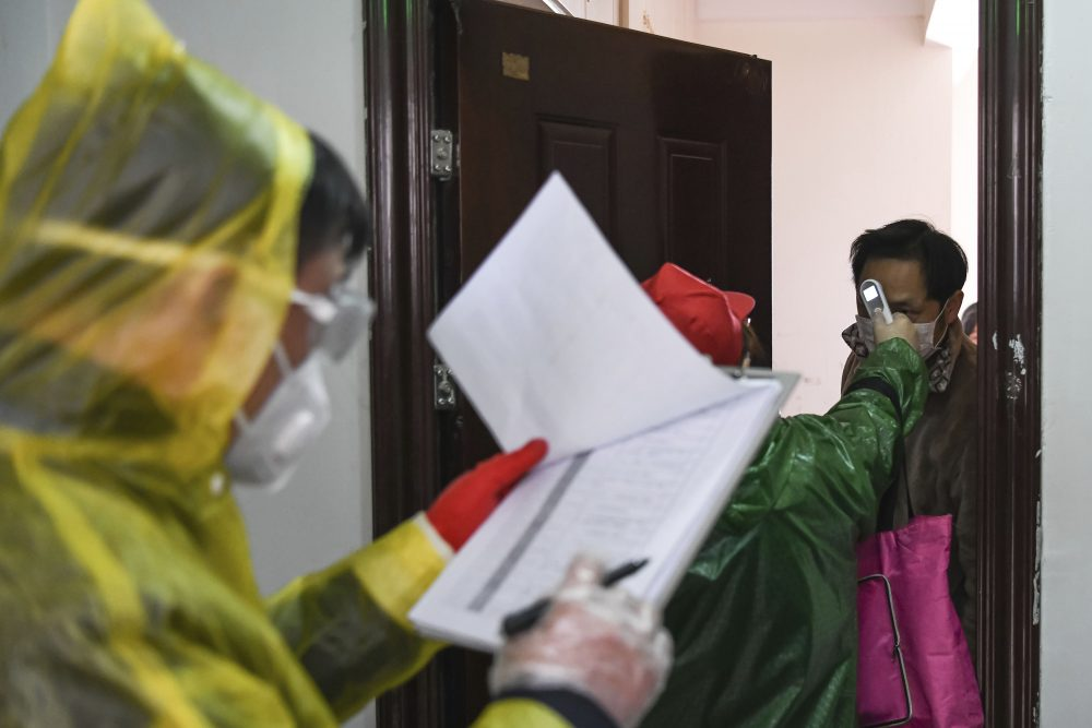 Workers go door-to-door to check the temperatures of residents during a health screening campaign in the Qingheju Community, Qingshan District of Wuhan in central China's Hubei Province, on Tuesday.