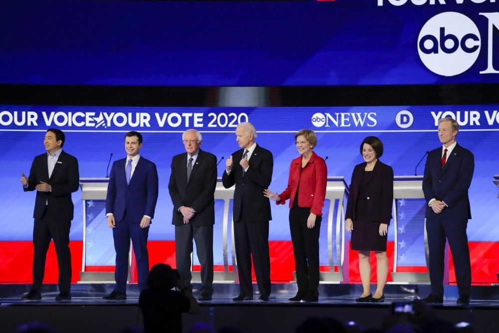From left, Democratic presidential candidates entrepreneur Andrew Yang, former South Bend Mayor Pete Buttigieg, Sen. Bernie Sanders, I-Vt., former Vice President Joe Biden, Sen. Elizabeth Warren, D-Mass., Sen. Amy Klobuchar, D-Minn., and businessman Tom Steyer stand on stage Friday before the start of a primary debate hosted by ABC News, Apple News and WMUR-TV at Saint Anselm College in Manchester, N.H.
