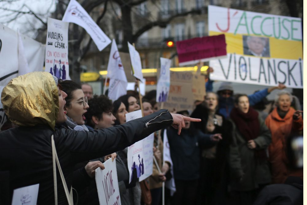 """Women demonstrate against multiple nominations for Roman Polanski outside the Cesar awards ceremony, the French equivalent of the Oscar, Friday in Paris. The poster at right reads, """"I accuse Violanski,"""" playing withe French word for rape and the name Polanski."""