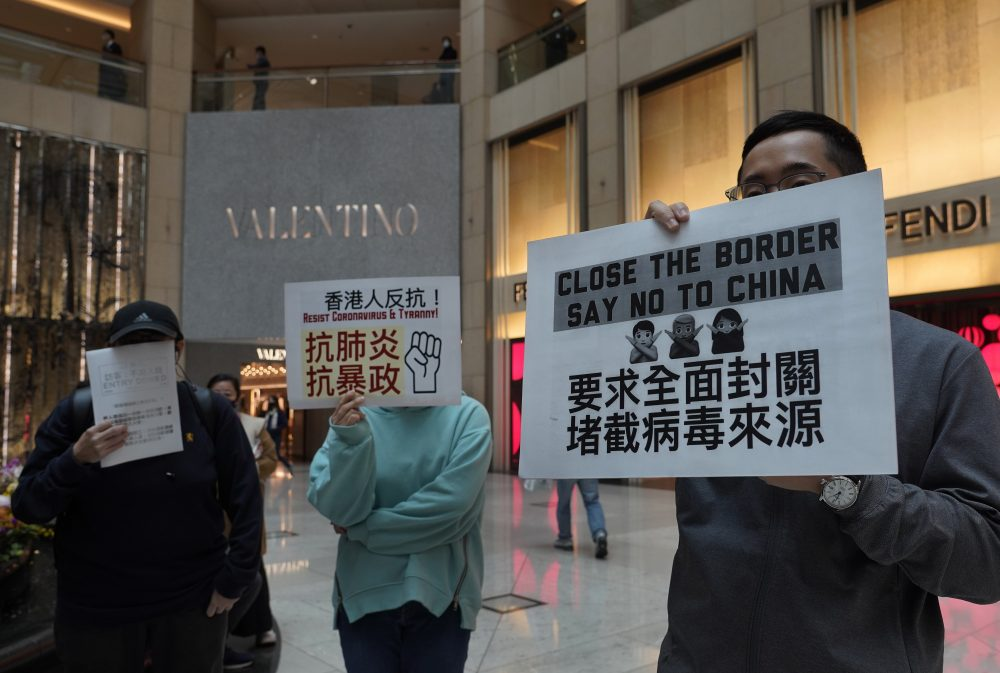 "Protesters hold placards reads ""Close the border, say no to China"" during a protest at a mall in Hong Kong on Tuesday."