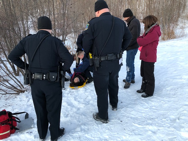 Emergency workers tend to a woman injured Saturday while sledding at Quarry Road Recreation Area in Waterville.