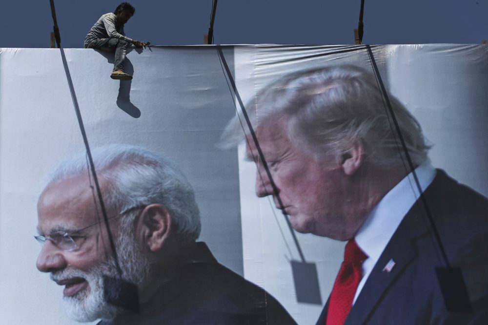 A worker installs a billboard image welcoming President Trump ahead of his visit, in Ahmadabad, India. Trump is scheduled to visit the city on Monday and Tuesday.