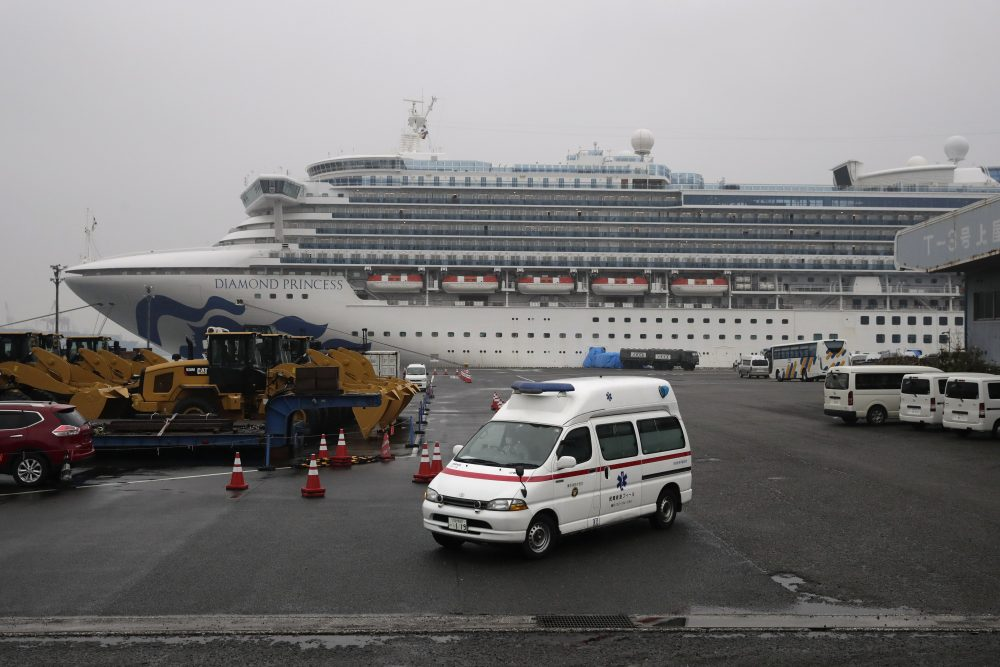 An ambulance leaves a port where the quarantined Diamond Princess cruise ship is docked Sunday in Yokohama, near Tokyo. The U.S. says Americans aboard the quarantined ship will be flown back home on a chartered flight Sunday, but that they will face another two-week quarantine.