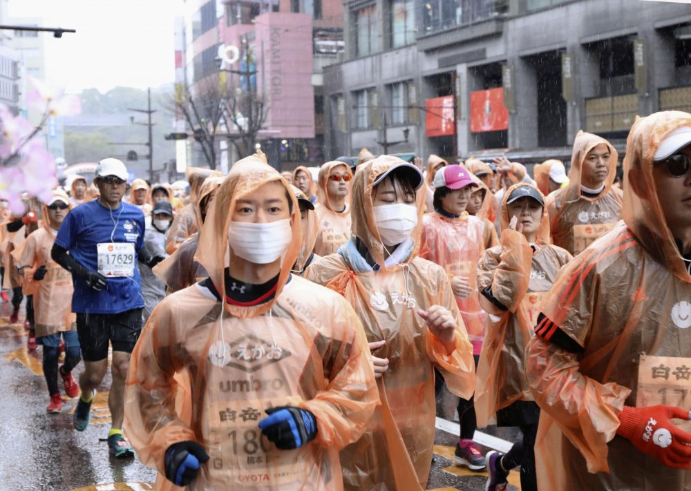 Runners - some wearing masks - compete in a marathon in Kumamoto in western Japan on Feb. 16. Organizers of the Tokyo Marathon set for March 1, are drastically reducing the number of participants out of fear of the spread of the coronavirus. The general public is essentially being barred from the race.