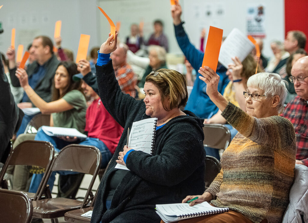 Sue Callahan, left, and her mother-in-law, Judy Callahan vote for an article in the Minot Town Meeting on March 7.