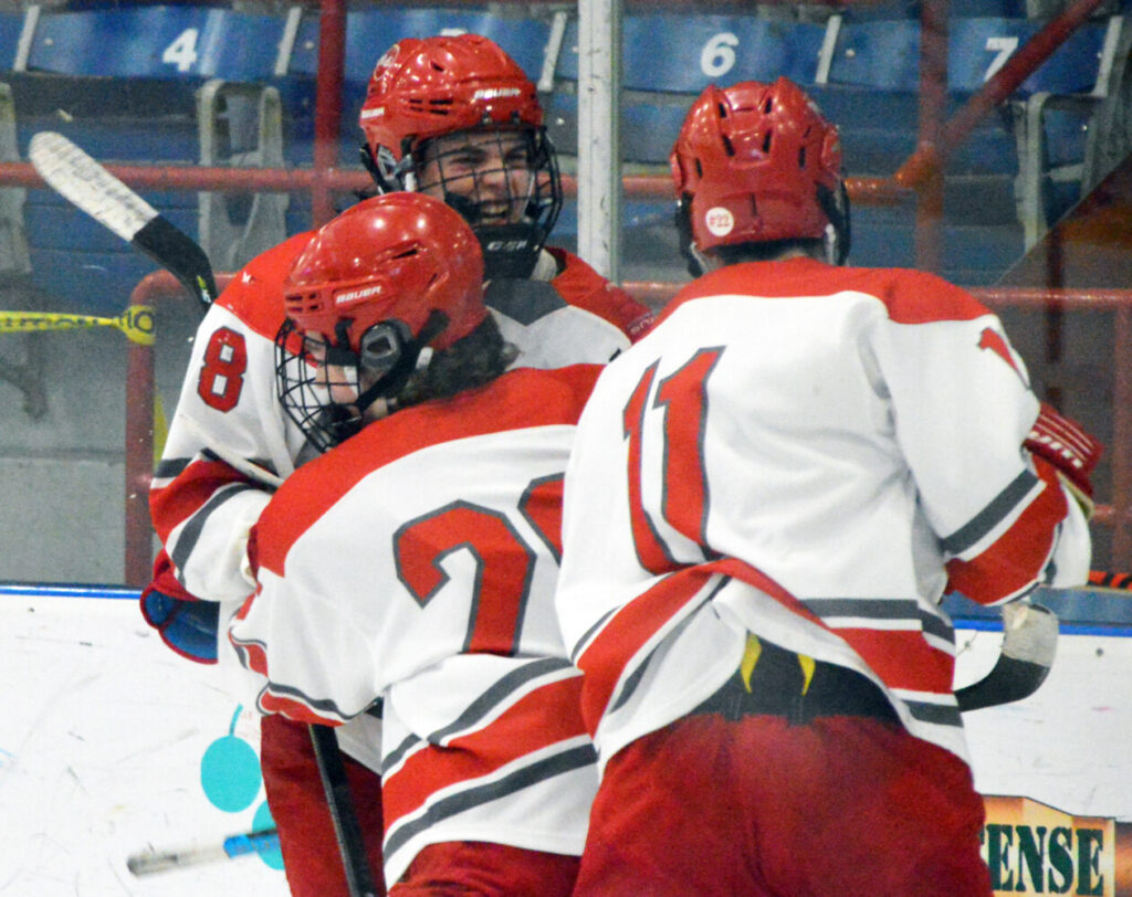 Eric Walker of South Portland/Freeport/Waynflete celebrates with teammates after scoring his team's third goal late in the second period. The Red Riots rallied to a 5-4 Class A quarterfinal victory over Thornton Academy at the Androscoggin Bank Colisee in Lewiston on Friday.