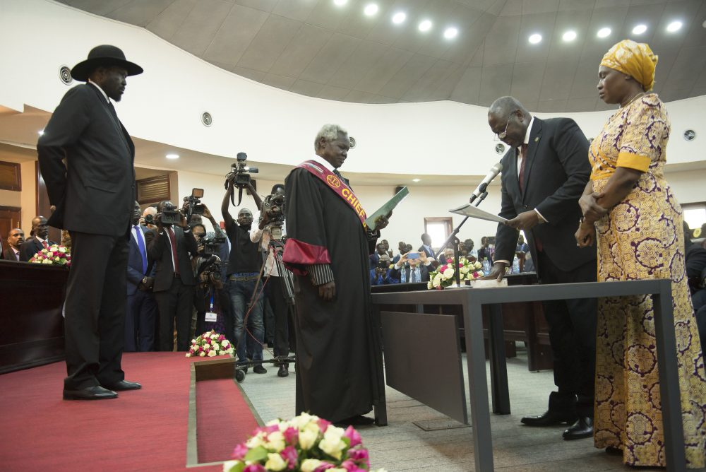 The president of South Sudan, Salva Kiir, left, swears in Riek Machar as the first vice president of South Sudan on Saturday. South Sudan opened a new chapter in its fragile emergence from civil war Saturday as rival leaders formed a coalition government.