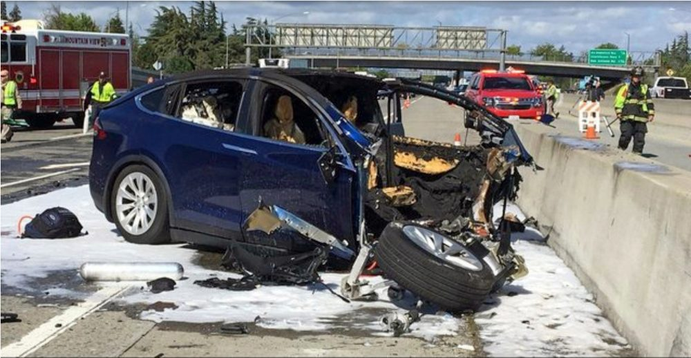 Emergency personnel work a the scene where a Tesla crashed into a barrier on U.S. Highway 101 in Mountain View, Calif., on March 23, 2018. The National Transportation Safety Board says Walter Huang, an Apple engineer who was driving the vehicle, was playing a video game on his smartphone at the time. The agency says the car's forward collision avoidance system didn't alert Huang.