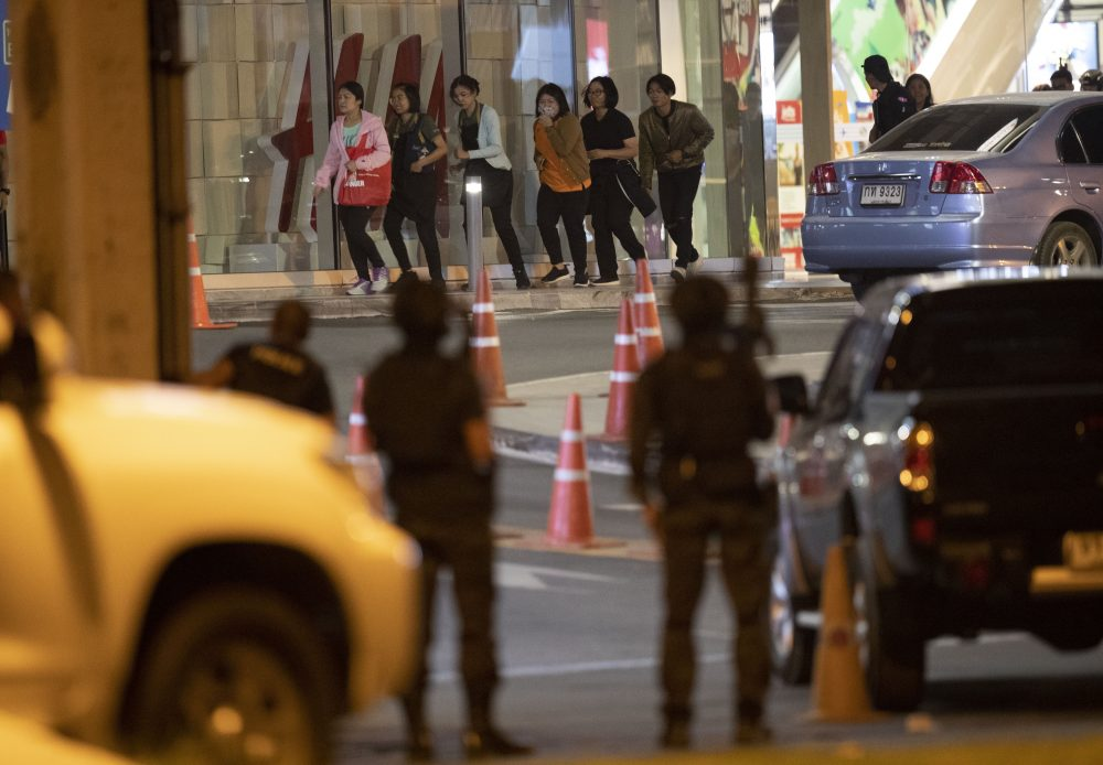 People who were able to get out of Terminal 21 Korat mall walk outside the building in Nakhon Ratchasima, Thailand on Sunday. A soldier who holed up in a popular shopping mall in northeastern Thailand shot multiple people on Saturday, killing at least 20 and injuring 31 others, officials said.