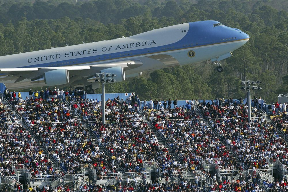 Air Force One rises above the packed grandstands along the super stretch at Daytona International Speedway in Daytona Beach, Fla., on Feb. 15, 2004. George W. Bush arrived before the race, talked with drivers along pit road and gave the command for drivers to start their engines.