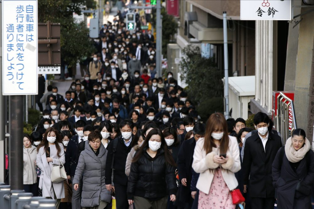 People wear masks  during morning rush hour on Feb. 20 in Tokyo. Prime Minister Shinzo Abe has called on companies to allow employees to work from home. Sri Lanka and Laos imposed price caps for face masks, while India restricted the export of personal protective equipment.