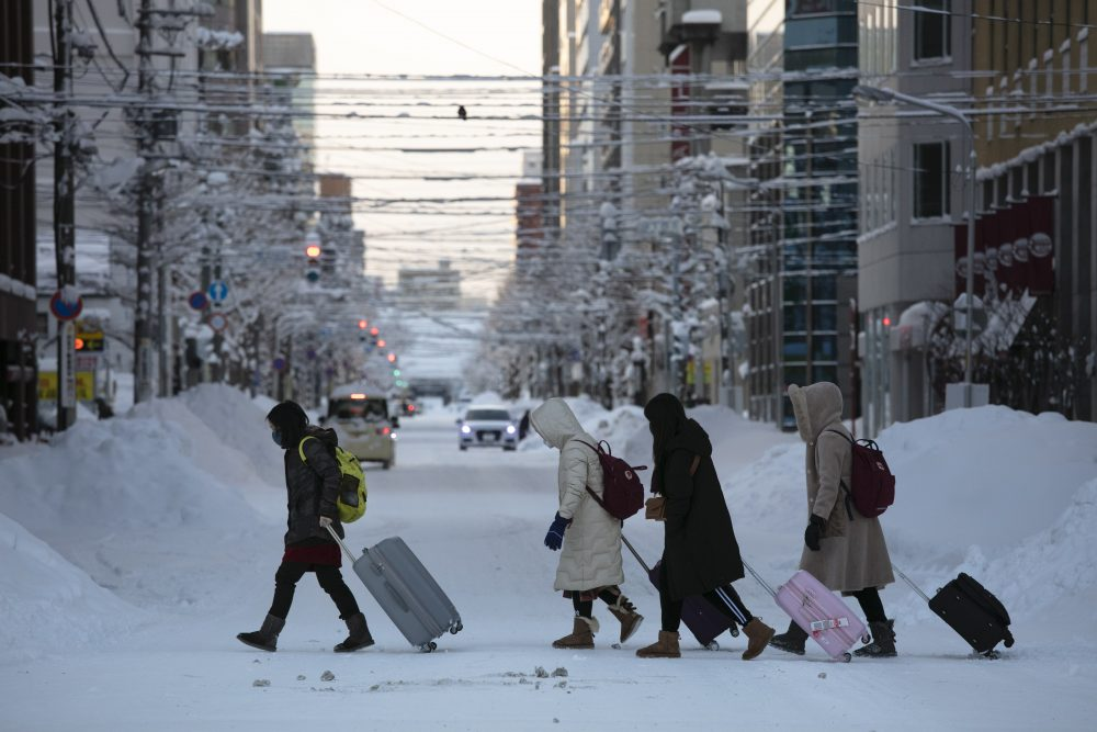 Tourists crosses an icy street with their luggage in Sapporo, Hokkaido, Japan, this month. The Japanese island of Hokkaido is declaring a state of emergency over the rapid spread of the new virus there.