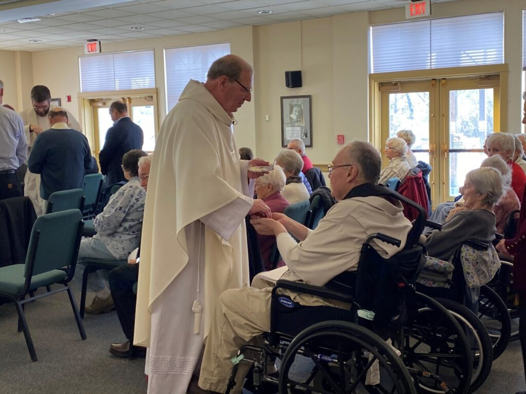 Bishop Robert P. Deeley gives communion Wednesday to a resident of the Mount Saint Joseph Retirement Home in Waterville.