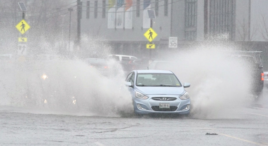 A car drives through standing water on Commercial Street in Portland on Thursday morning.