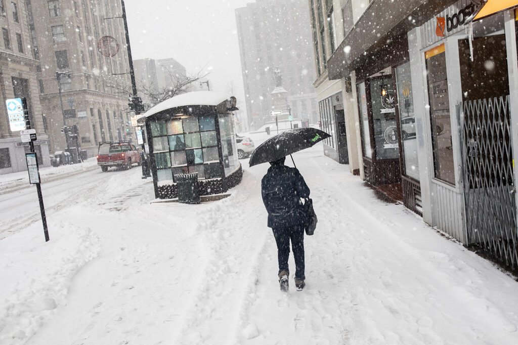 A woman walks with an umbrella to protect her from the blowing snow in downtown Portland  Thursday morning.