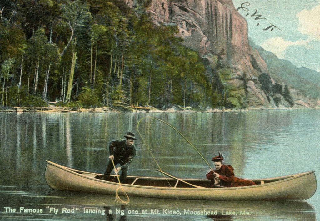 """A postcard of """"The famous 'Fly Rod' Crosby Landing a Big One at Mt. Kineo, Moosehead Lake."""" The postcard was sent in 1908."""