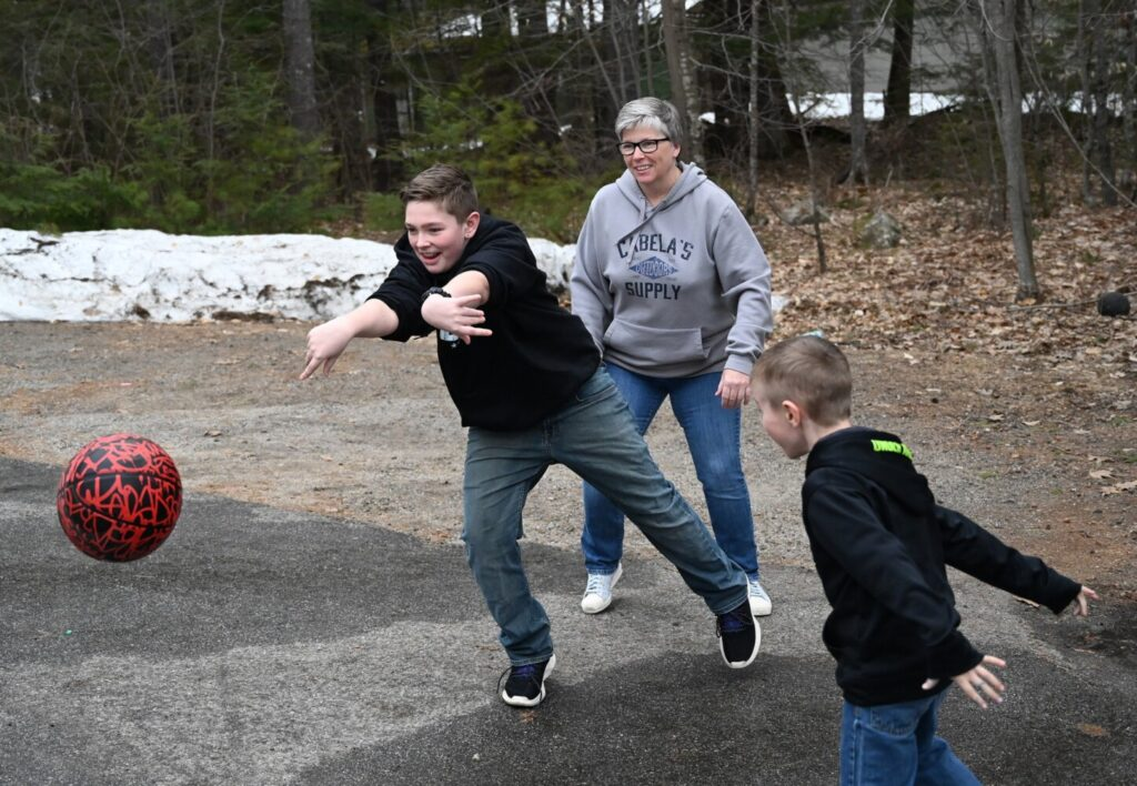 Barb Childs of Waterboro looks on as Wyatt 13, passes the basketball during a game at Childs' home. To the right is Gavin, 6.