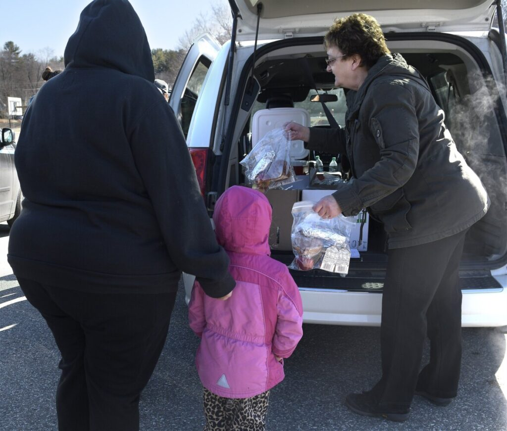 Augusta schools food service worker Sue Briggs serves bagged meals to children Monday morning at Williams Playground in Augusta. The food service department is preparing meals to students who aren't attending school, which has been canceled because of the coronavirus outbreak.