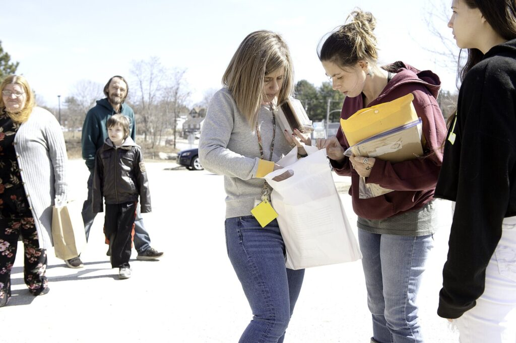 """Emily Braga, center, shows Catherine Hughes the learning materials inside the learning packet Hughes picked up for her children at Fairview Elementary School in Auburn on Wednesday. Public elementary schools throughout Auburn handed out the packets to each student so they have materials to work on during school shutdowns due to the coronavirus. """"This is amazing. I was nervous about the school thing,"""" said Hughes, the mother of two Fairview students and one high school freshman, Kiara Richards, right. """"Now we can be somewhat normal and the kids' schedule won't change as much,"""" Hughes said. Auburn Mayor Jason Levesque stopped at Fairview on Wednesday. """"I plan to hit two schools a day to help when I can,"""" he said. """"But the teachers got this down and have taken care of it all. My big thing is to find any holes that I can help with, but things are going amazingly well,"""" he said."""