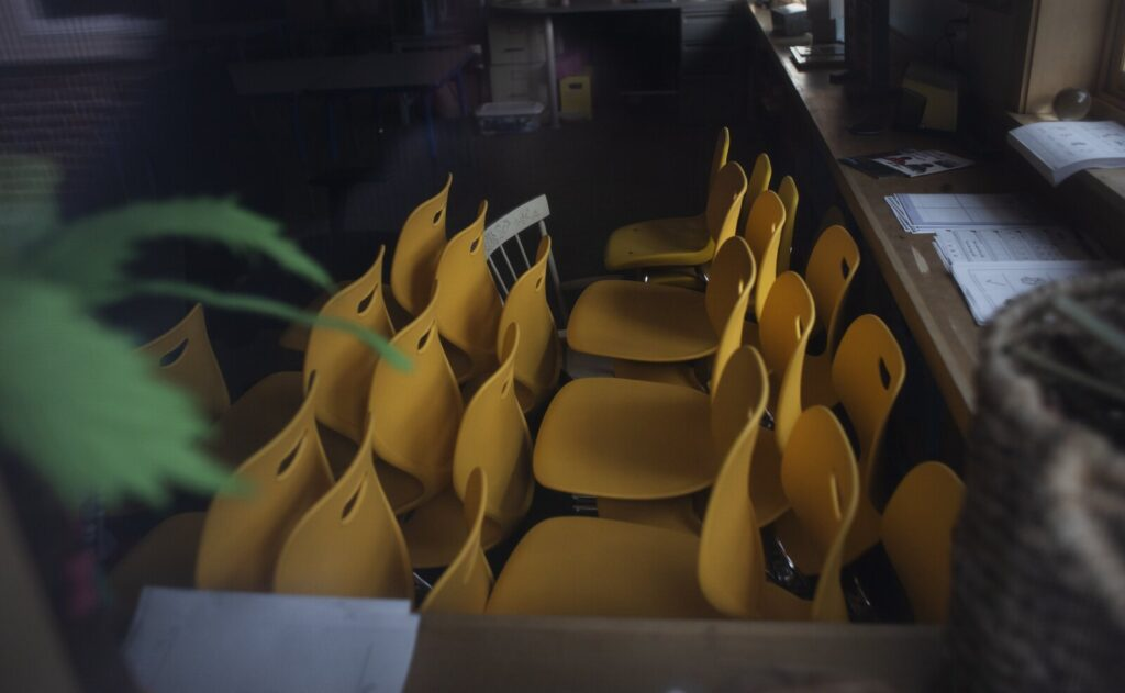 Students' chairs are stacked in a vacant classroom March 20 at Eight Corners Elementary School in Scarborough. Maine's education commissioner is advising school districts to plan to keep their classrooms closed for the rest of this academic year.