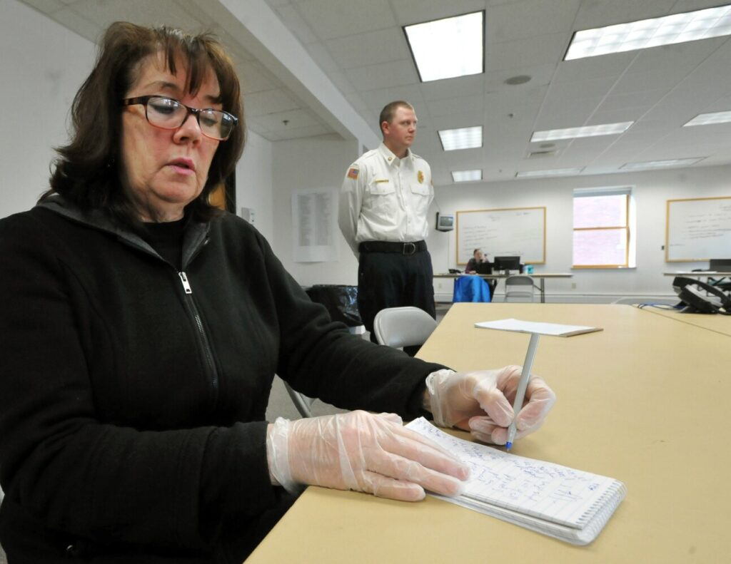 Waterville Morning Sentinel reporter Amy Calder wears protective gloves Monday as she reports on the coronavirus pandemic at the new Emergency Operations Center at the Waterville Fire Department. Calder was screened with another journalist before being allowed access to the building.