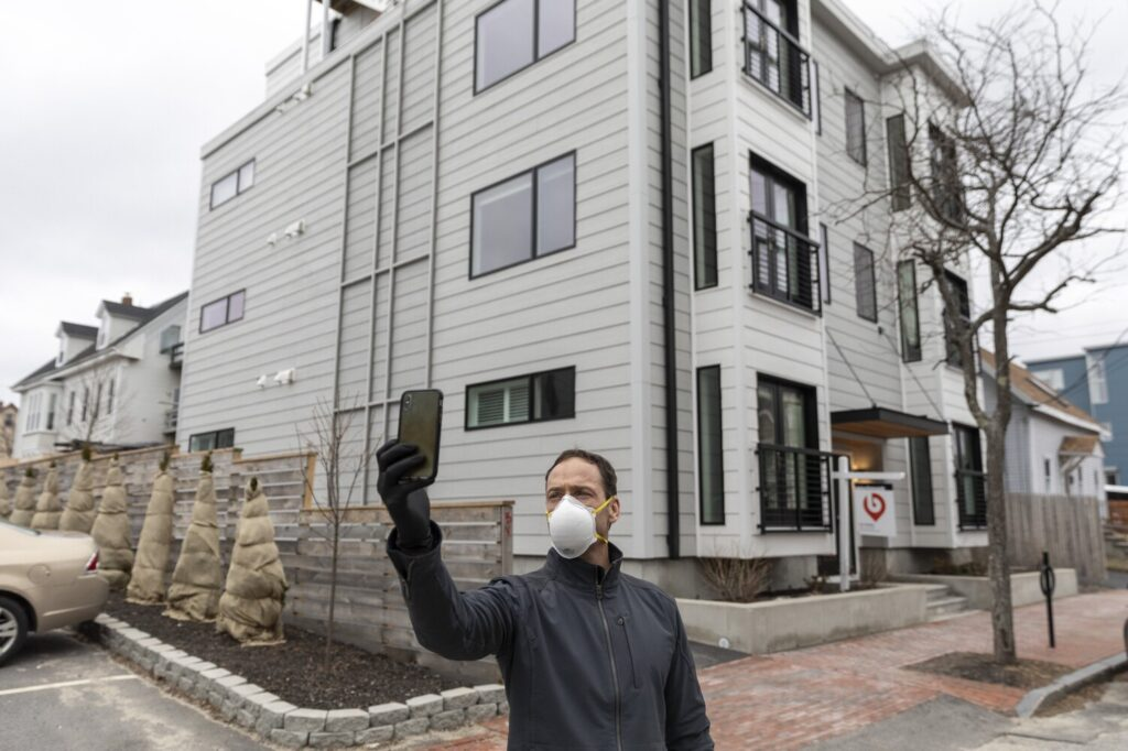 Tom Landry, broker and owner of Benchmark Real Estate, starts a Facebook Live video tour of a condo for sale in the East End of Portland on Monday. The coronavirus outbreak has created uncertainty for home sellers, buyers and real estate professionals.